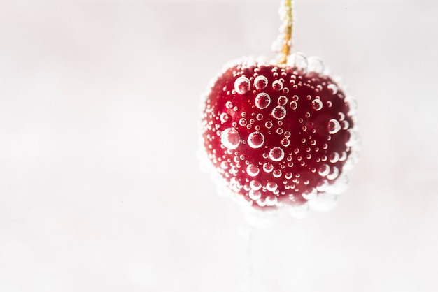 Water drops on juicy red cherry Free Photo