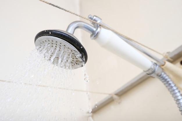 ライムスケールのセラミックハンドルが付いた古いシャワーヘッドから流れる水は、交換または脱灰する必要がありました。 Premium写真