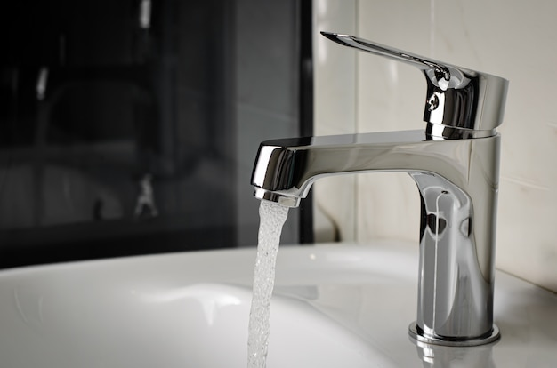 Water flows from the tap or faucet in bathroom. copy space, close up Premium Photo