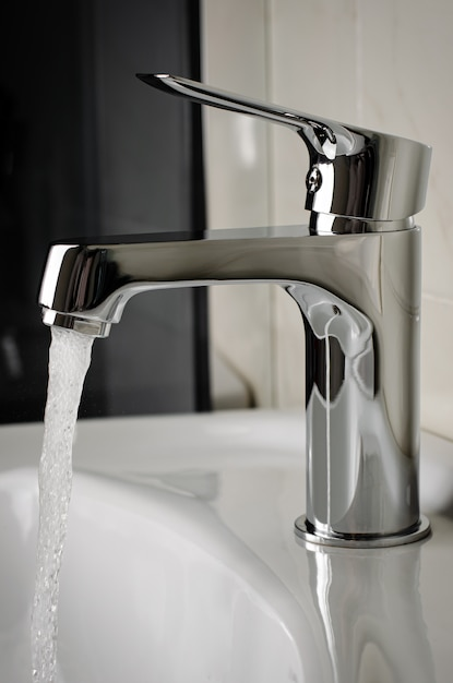 Water flows from the tap or faucet in bathroom Premium Photo
