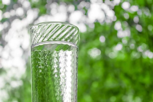 Вода в стакане прозрачного стекла на фоне окна Premium Фотографии