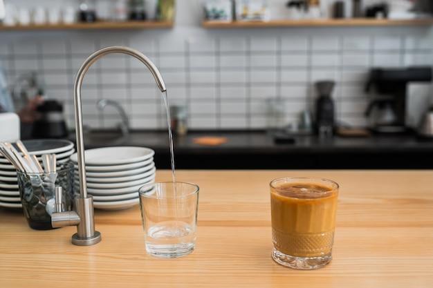 L'acqua sta versando da un rubinetto in un bicchiere Foto Gratuite