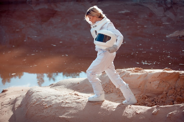 Water on mars, futuristic astronaut without a helmet in another planet, image with the effect of toning Premium Photo