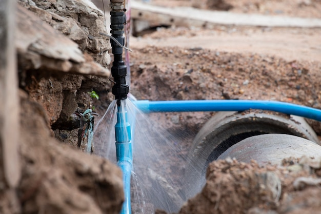 Water pipe break .exposing a burst water main, focused on the spraying water and the pipe. Premium Photo