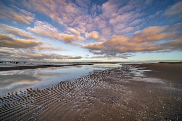 Stagno d'acqua in riva al mare sotto un cielo nuvoloso blu Foto Gratuite