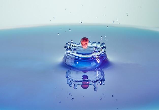 水のしぶきのクローズアップ、色付きの滴と王冠の作成の衝突、抽象的な効果を持つコンセプトアート。 Premium写真