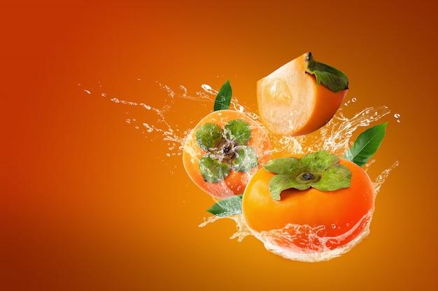 Water splashing on fresh persimmons on orange background Premium Photo