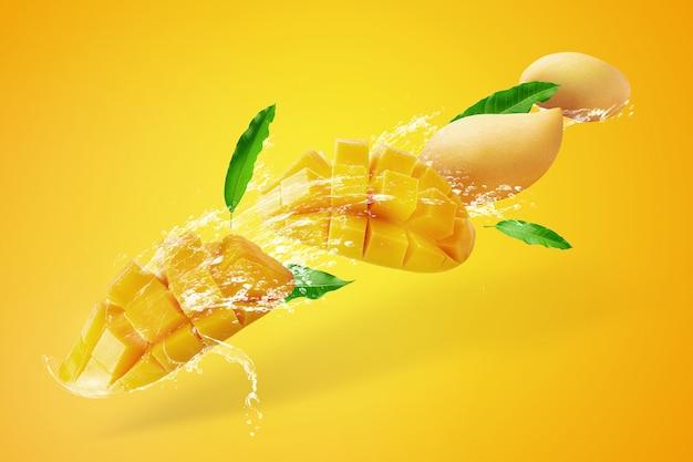Water splashing on fresh sliced mango fruit with mango cubes isolated on yellow Premium Photo