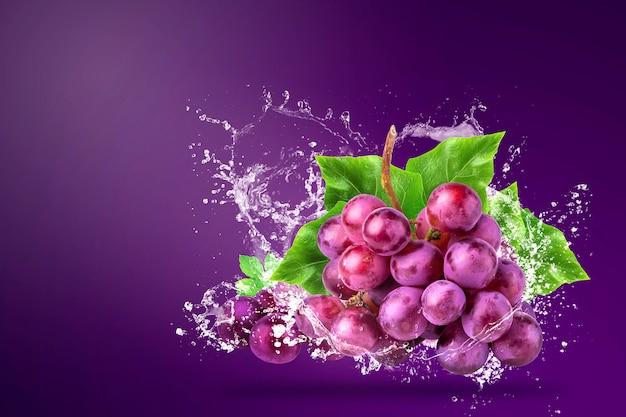 Брызги воды на свежий красный виноград над фиолетовым Premium Фотографии