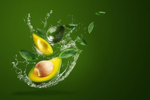 Вода брызгая на свежем отрезанном зеленом авокадое над зеленой предпосылкой. Premium Фотографии