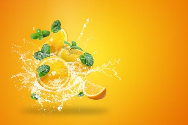 Вода брызгает на свежие нарезанные фрукты апельсины Premium Фотографии