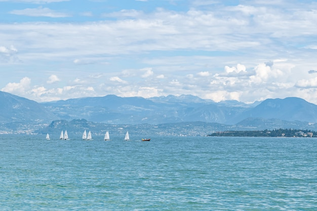 Водная гладь озера с белыми парусниками и горным хребтом на горизонте Premium Фотографии