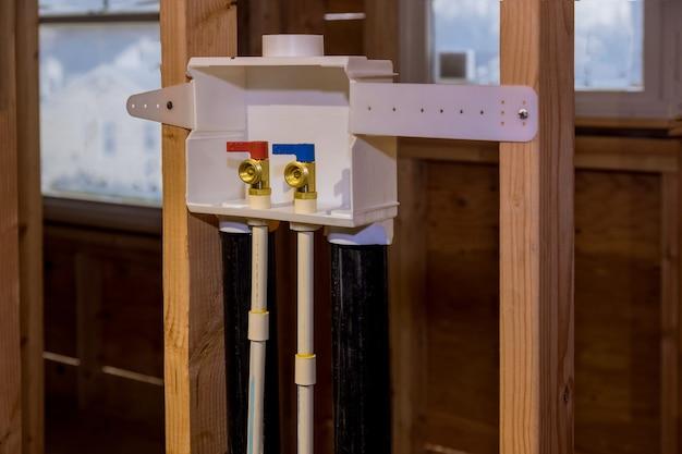 洗濯機に水を接続するための新しい家に洗濯コンセントボックスを設置する際の自宅の給水システム Premium写真