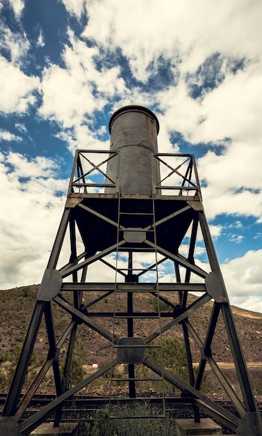 Water tank in the iron structure with the sky and mountain Premium Photo