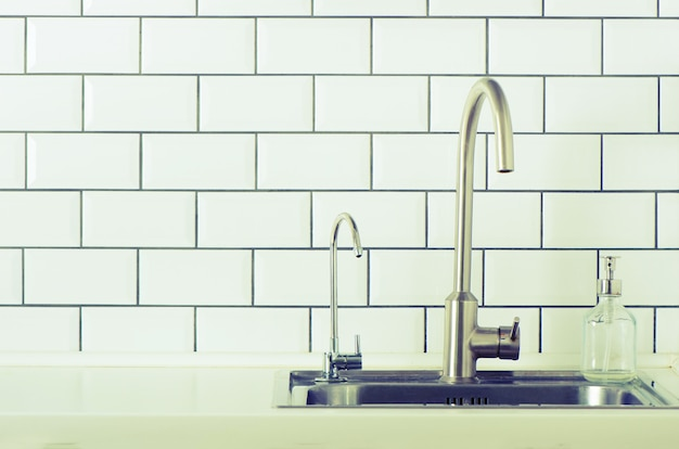 Water tap. white kitchen design. mixer tap with flowing water on brick tile background. potted green plants. Premium Photo