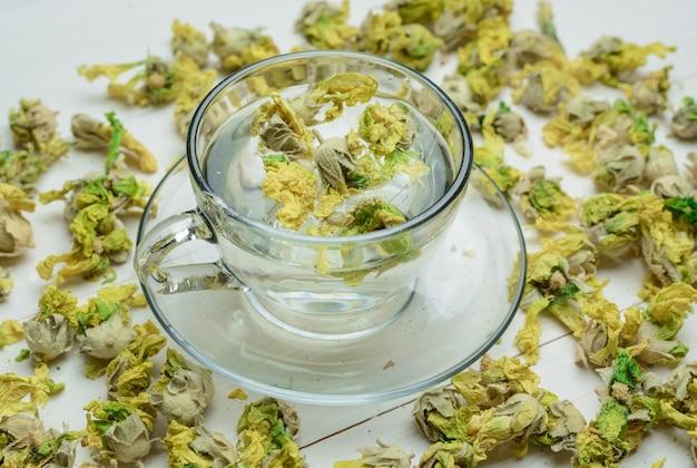 Innaffi con le erbe secche in una tazza sulla tavola di legno, vista dell'angolo alto. Foto Gratuite
