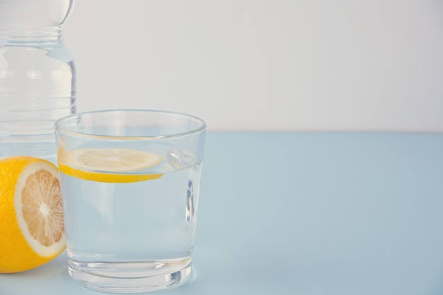 Water with lemon on the blue table Premium Photo