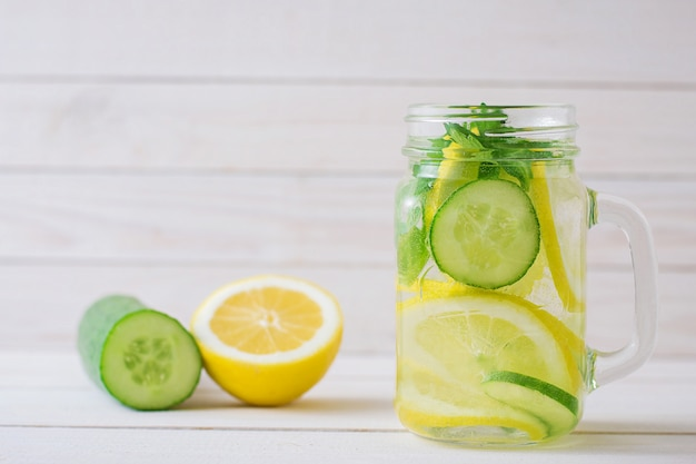 Water with lemon and cucumber in a glass cup Premium Photo