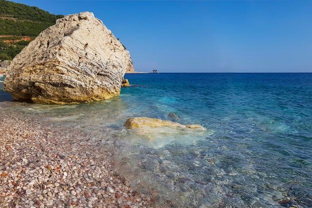 澄んだ紺waterの水と層状岩の小石のビーチのパノラマビュー Premium写真