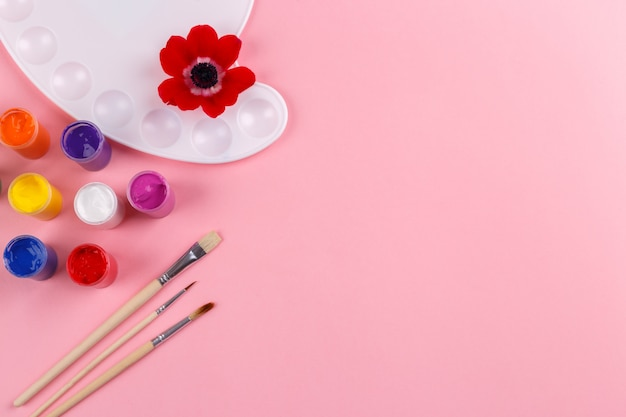 Watercolor palette and brushes on pink background Premium Photo
