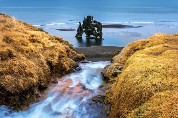 滝とhvitserkurは、アイスランドの北海岸の海にある壮観な岩です。 無料写真