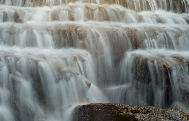 Waterfall flowing into a line of rocks. Premium Photo