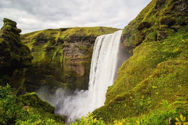 Waterfall between green mountains Free Photo