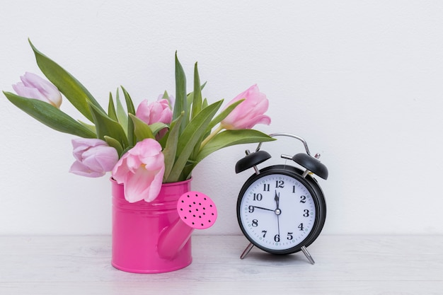 Watering pot with flowers and clock Free Photo