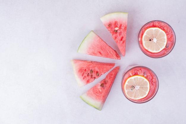 白地に赤いフルーツスライスのスイカジュース。 無料写真