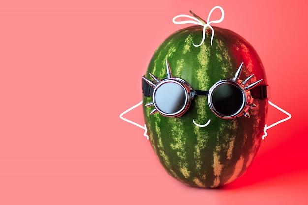 A watermelon punk in rocker glasses on pink background Premium Photo