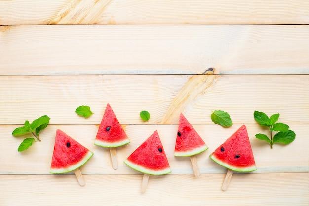 Watermelon slice popsicles on brown wood Premium Photo