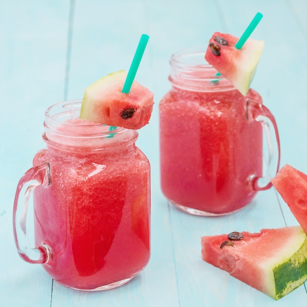 Watermelon smothie and slices on blue background Premium Photo