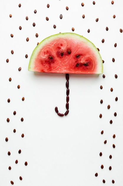 Watermelon umbrella with seeds on white background Free Photo