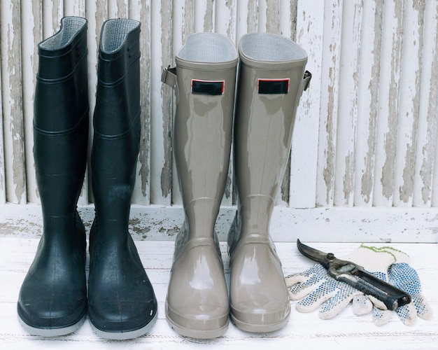 Waterproof boots and pruner on white wood Free Photo