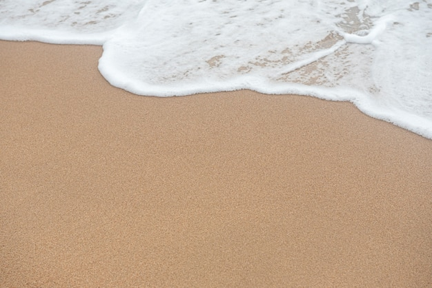 Wave and sand beach background with copy space. Premium Photo