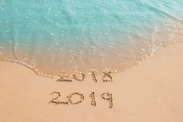 Wave washing away inscription 2018 Free Photo