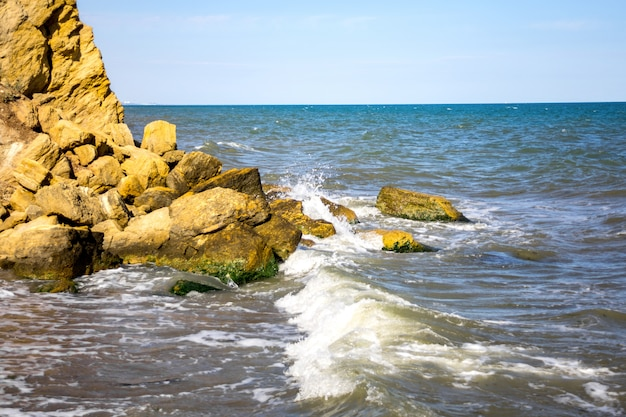 Waves beat against stones on a sunny day Premium Photo