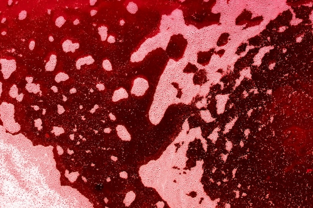 Waves of bubbles on red colored liquid Free Photo