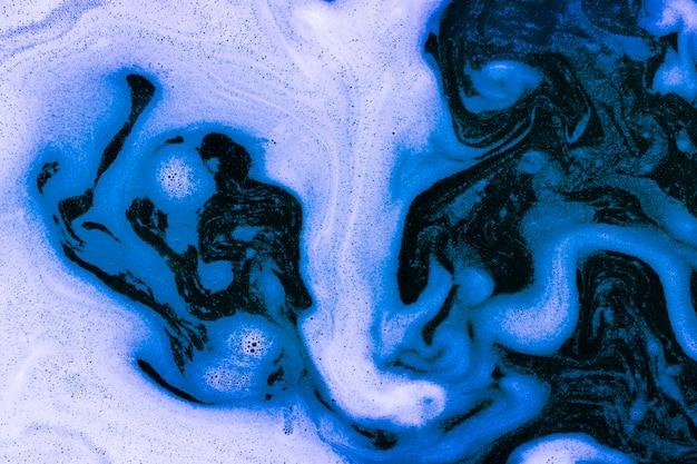 Waves of foam on blue liquid Free Photo