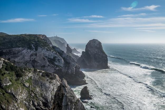 青空の下で岩の多い海岸線に打ち寄せる海の波 無料写真