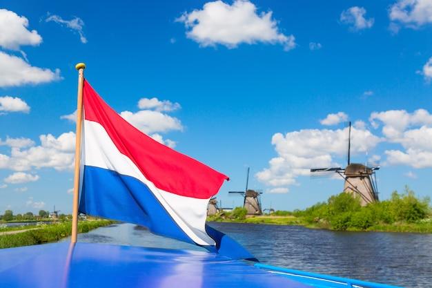 オランダのキンデルダイク村の有名な風車に対してクルーズ船にオランダの旗を振る Premium写真