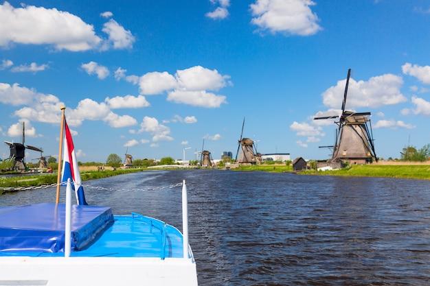 オランダのキンデルダイク村の有名な風車に対してクルーズ船にオランダ国旗を振る。 Premium写真
