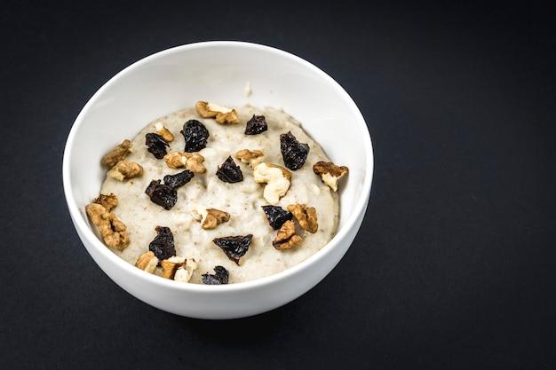 オーツ麦と一緒に牛乳をゆで、プラムとクルミを加えました。クルミ、プルーン、シナモン、砂糖を使ったオートミールのレシピ。 Premium写真