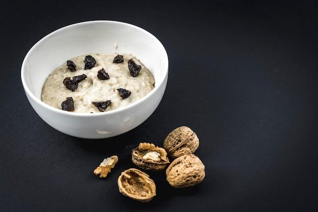オート麦と一緒に牛乳を煮て、梅を加えました。クルミ、プルーン、シナモン、砂糖を使ったオートミールのレシピ。 Premium写真