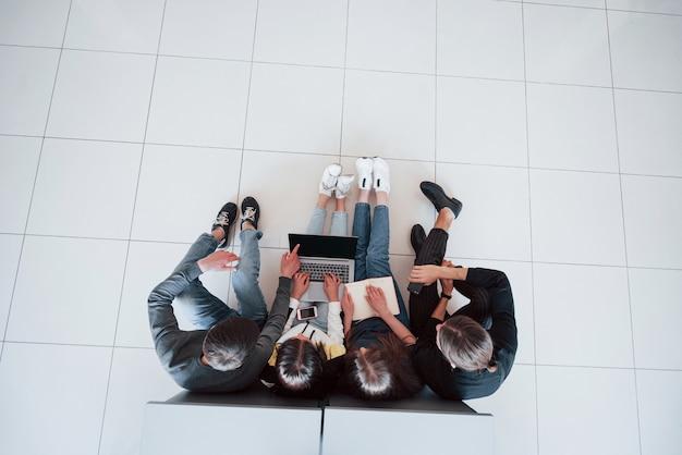 これが使えます。近代的なオフィスで働くカジュアルな服装の若者のトップビュー 無料写真