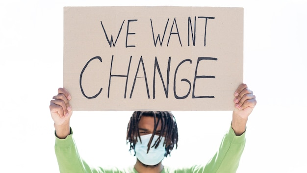 We want change quote on cardboard held by young person Premium Photo