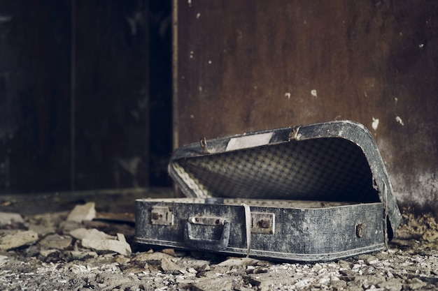放棄された廃屋の中の風化したスーツケース 無料写真