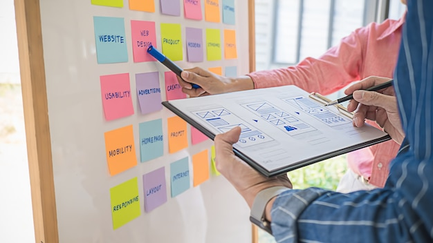 Web designer brainstorming for a strategy plan. colorful sticky notes with things to do on office board. user experience (ux) concept. Premium Photo