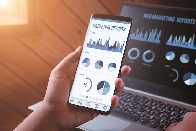 웹 마케팅 관리 및 보고서. 잡고 스마트 폰보고 및 휴대 전화 및 노트북 화면에 마케팅 보고서를보고 사람의 근접 후면보기. 프리미엄 사진