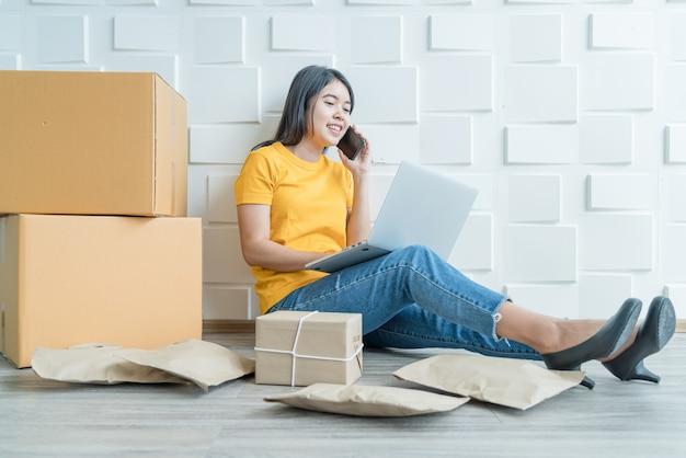 若いアジアのビジネスは、コンピューターを使用して電子メールまたはwebサイトから顧客の注文をチェックし、パッケージを準備するためのオンライン販売者の所有者を立ち上げ Premium写真